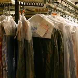 clothes in clear plastic dry cleaner bags on a rack