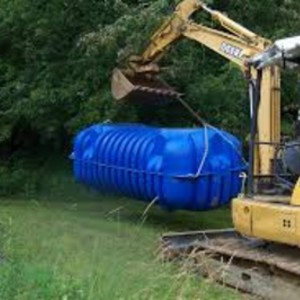 large blue septic system being lifted by heavy equipment