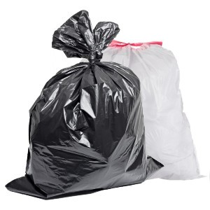 two plastic trash bags full of garbage, one bag black, one bag white